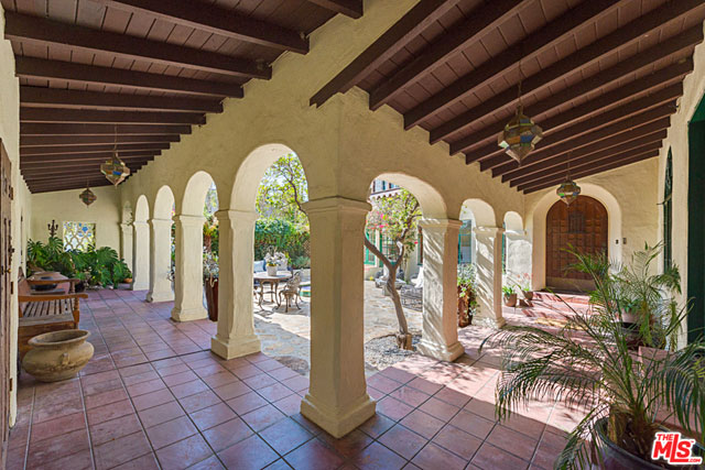 …this magnificent courtyard with arcades running along two sides, which feature tiled walkways and wood beam ceilings.