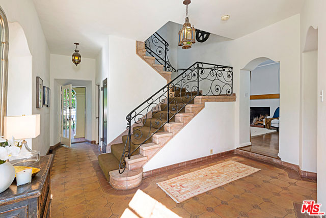 The front door of the home opens to a large foyer, from which one may walk into the living room, the library, the dining room, the kitchen, the back patio, or upstairs via a staircase that features an intricate wrought iron railing.