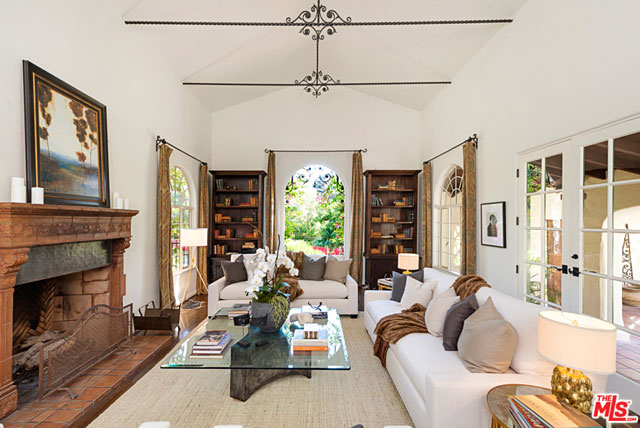 The step-down living room features a 17-foot cathedral ceiling with wrought iron ornamentation, a large fireplace, and loads of natural light thanks to the huge arched windows and French doors.