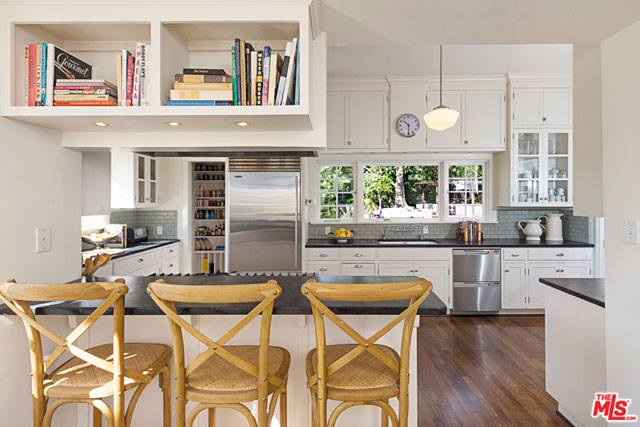 The one place in a home where a bit of modernism is most important is the kitchen and the choices made for the updates to this one are outstanding, starting with the open breakfast counter that leads into it.