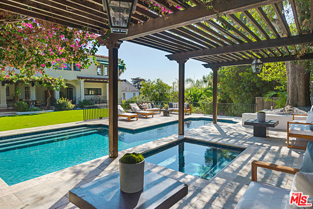 The patio steps down onto a large perfectly flat lawn, which leads to backyard oasis featuring a pool, spa and a spacious lounge area.