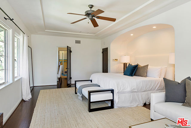 The spacious master bedroom overlooks the back yard and features an adjoining sitting area/office, which opens to a balcony and enjoys views of the downtown LA skyline.