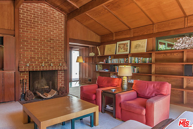 Tall, beamed ceilings, a brick fireplace and built-in shelving are among the features of this spacious living room.