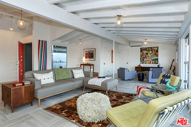 Inside, the main living areas of the house feature a completely open floor plan with a post and beam ceiling and marble tiled flooring. With a wall of glass along its eastern side, the spacious living room is flooded with natural light.