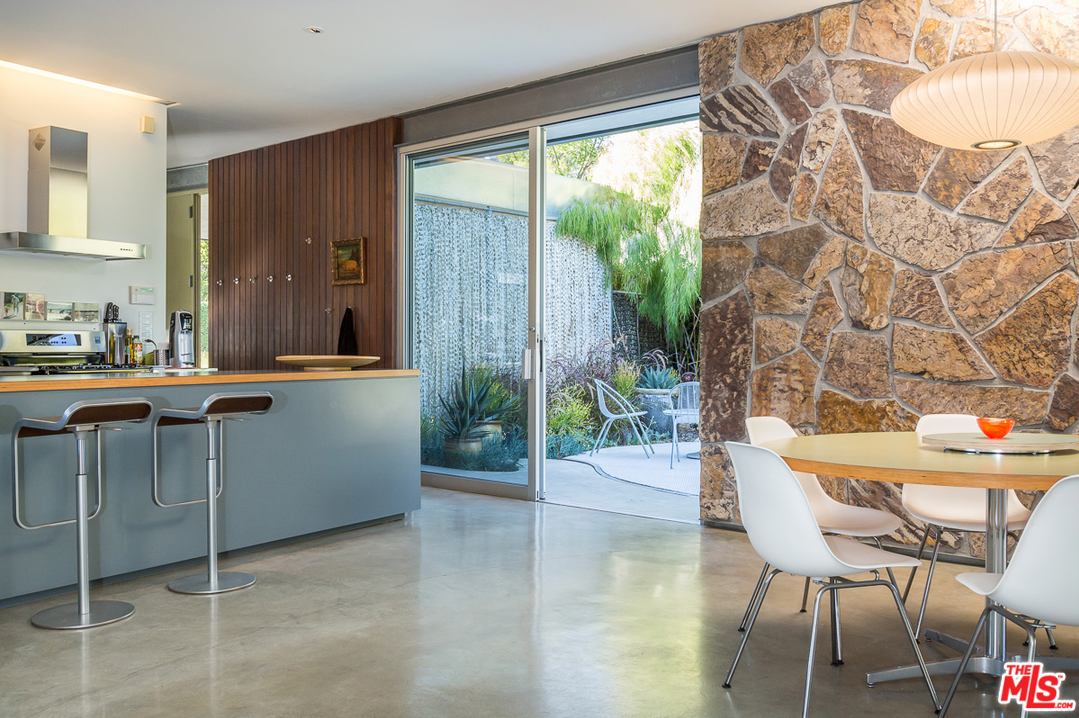 Douglas fir and a mosaic-like wall of stacked stone flank either side a sliding glass door that leads to a patio. Not only is this variety beautiful, but it works especially well as a way to frame the lush oasis that's found in the yard.