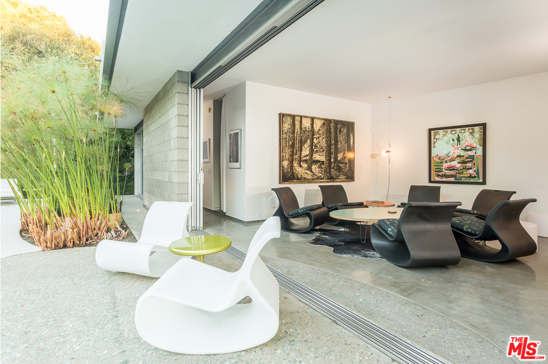 Polished concrete floors with radiant heating warm the home in winter, and in the warmer months the lines between indoors and outdoors are blurred thanks to a massive wall of glass that retracts and disappears. A great little touch that contributes to this blurring is the curved line of the terrazzo on the patio, which extends into the living room. Awesome.