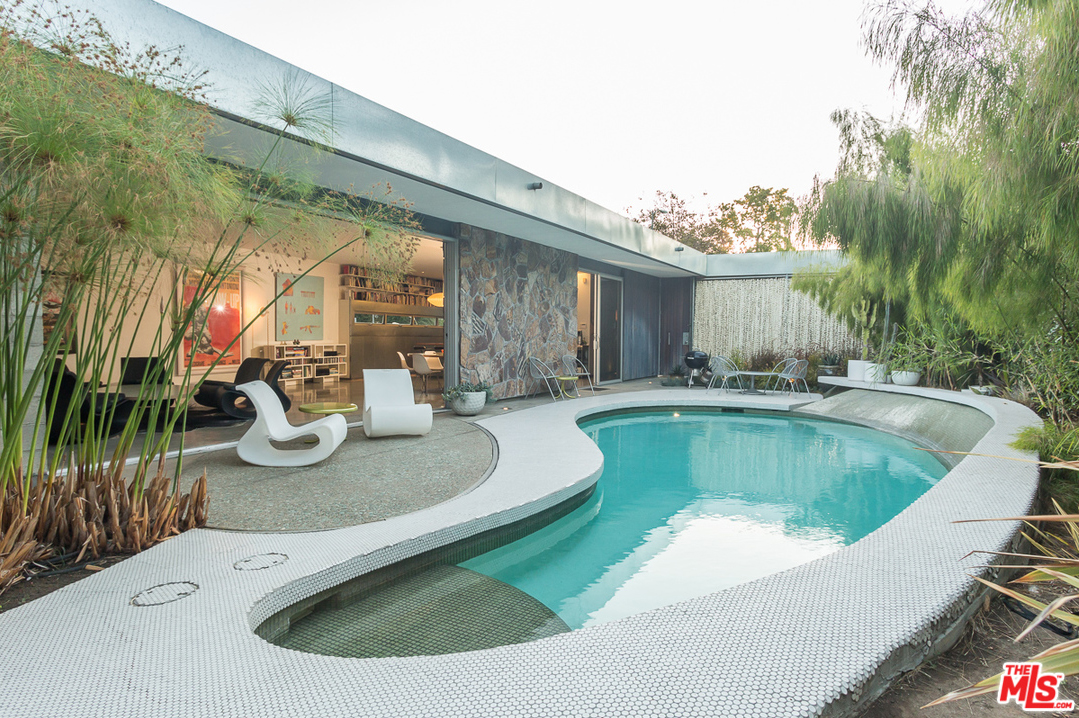 Here is the feature that I love the most. From overhead this may look like just another kidney shaped pool, but it's much more than that. The pool has a sloped wall that extends, in a swooping fashion, about a foot about above waterline on one side. A white, penny-round tiled deck surrounds the pool and its high side extends in a cantilevered fashion above the low side. (see far end in the photo above)