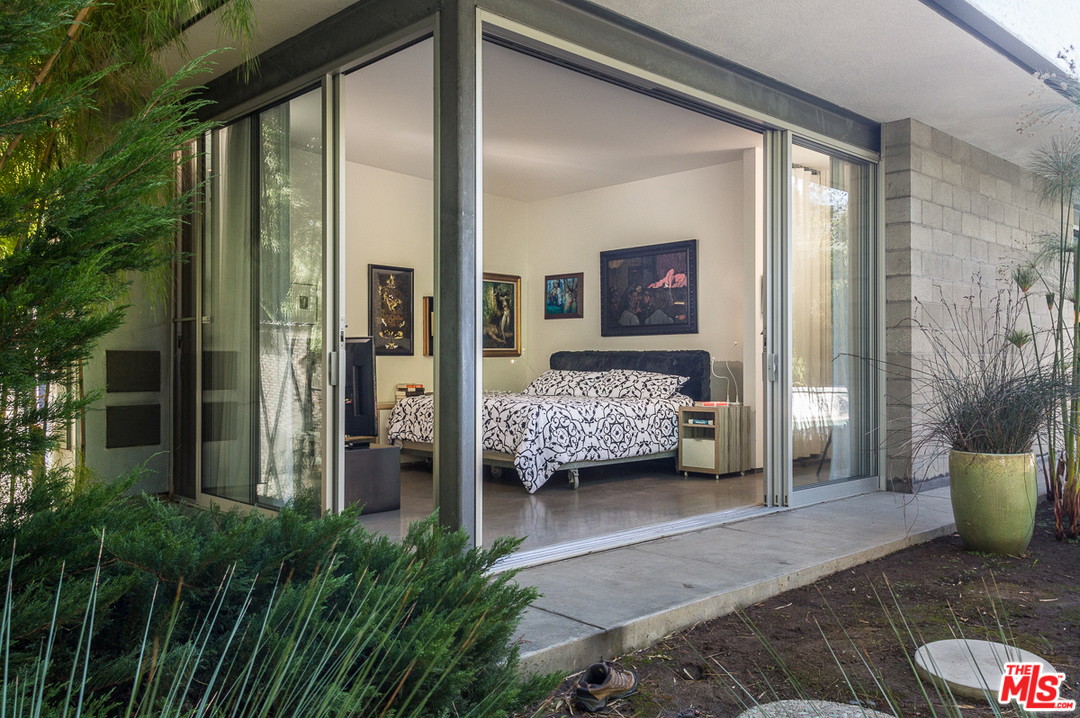 The master bedroom, which also features walls of glass on two sides, is designed to fully enjoy the lush yard outside. And you'll notice the continued variety of materials that are used for the exterior walls. Clearly, nothing about the design of this home was done as an afterthought.