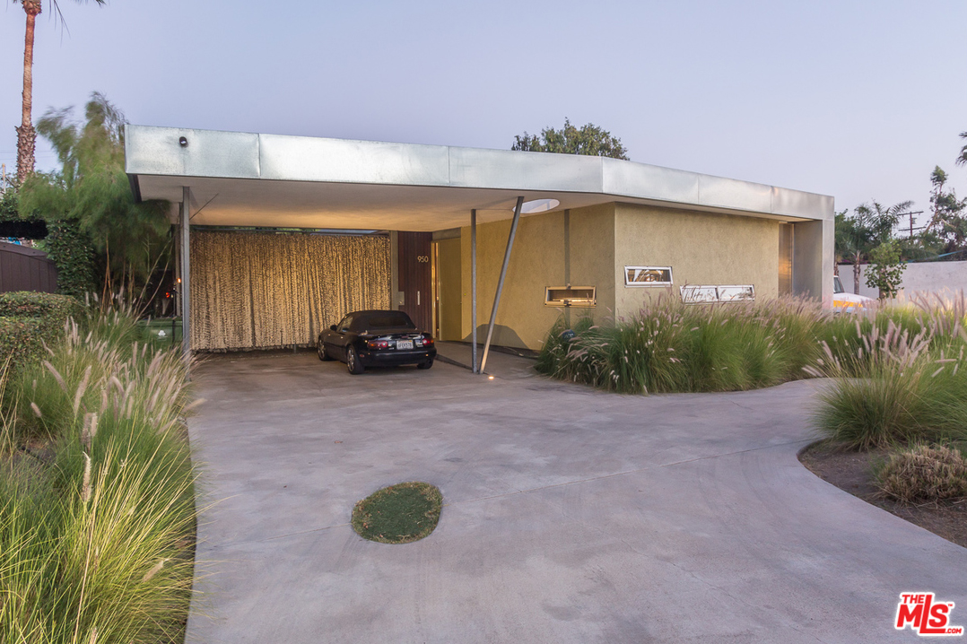The carport with it's V-shaped supports has a classic mid-century feel to it. And the concrete driveway with a random patch of grass is just perfect.