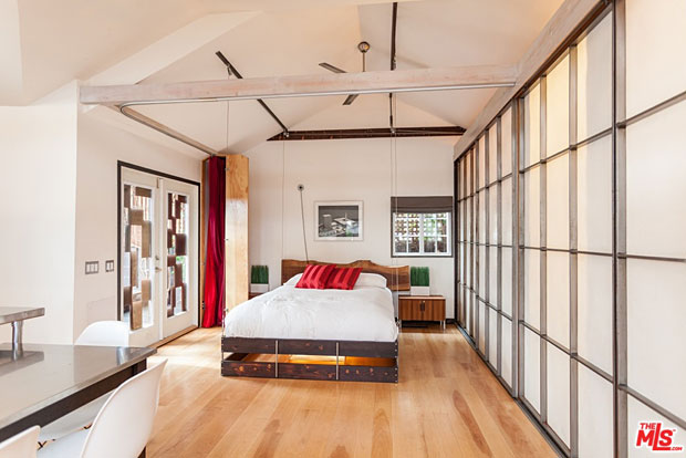 …the room is transformed into a bedroom. The light fixture is built into the bottom on a bedframe, which is raised and lowered using a weighted system of pulleys. And the wall-mounted desk, swivels downward to become a headboard.