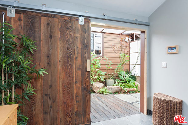 The shower room is closed off by this gorgeous, oversized sliding door made from reclaimed wood.