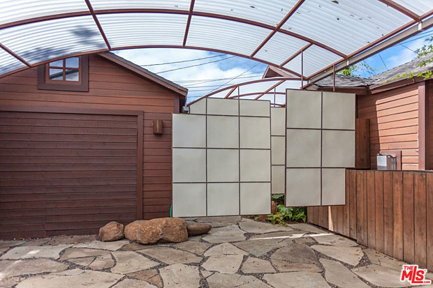 Once again, Shoji-inspired screens are used to great effect. Here, a series of them are suspended from above and arranged in an overlapping layout to provide an elegant separation between the carport and the patio.