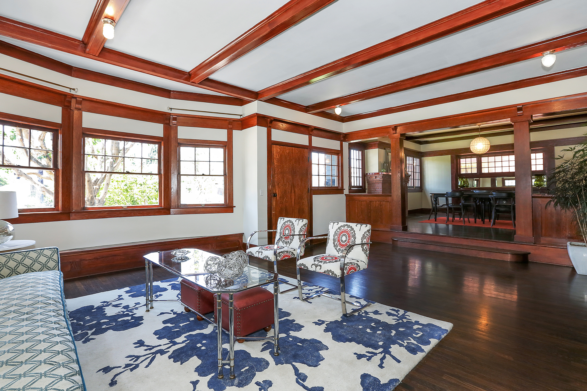 The main floor boasts five rooms, including a huge living room that receives loads of natural light through its picture window. One of my favorite features of the home is the raised dining room, whose entry is flanked by gorgeous wood columns.