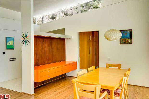 This short wall, which is lined with walnut and features sting-ray orange built-ins, serves as a divider between the entry and the dining room making it functional, beautiful and badass all at the same time. Up above, clerestory windows bring in light and give view to foliage on the opposite hillside.