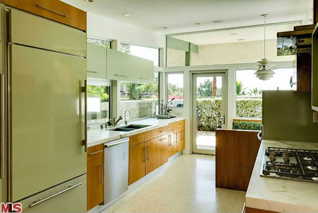 This kitchen is totally updated from top to bottom and it rocks. The floors are lined with gleaming terrazzo and it includes top-of-the-line appliances include a wine fridge. But I think my favorite touch may be the avocado green fridge.