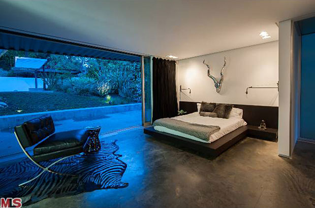 Two spacious bedrooms are at the back of the house and both open up to the back yard, which features a large infinity style swimming pool surrounded by lush greenery, giving it complete privacy.