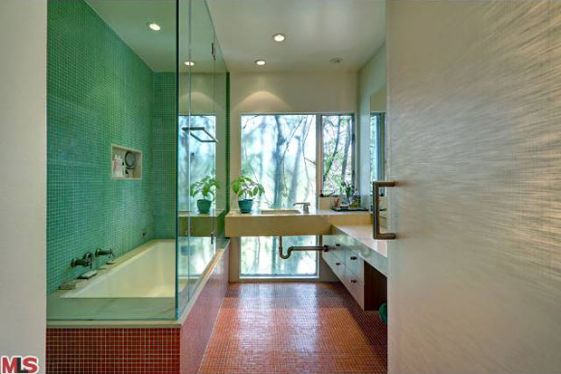 This bathroom alone is worthy of a blog post. Almost everything about it represents thinking that is outside the box. Rather than sheetrock and wood, the hallway wall and door that mark its entry are made of glass, whose textured surface makes it entirely opaque while still allowing a sense of space beyond it. Inside the bathroom, the wall facing the outside is also glass, this time transparent enough for the foliage outside to be enjoyed and compliment the green of the room's finishes. And perhaps my favorite feature of the room is the sink, which juts out from the wall with exposed plumbing on the underside. That is way cool and practical at the same time.