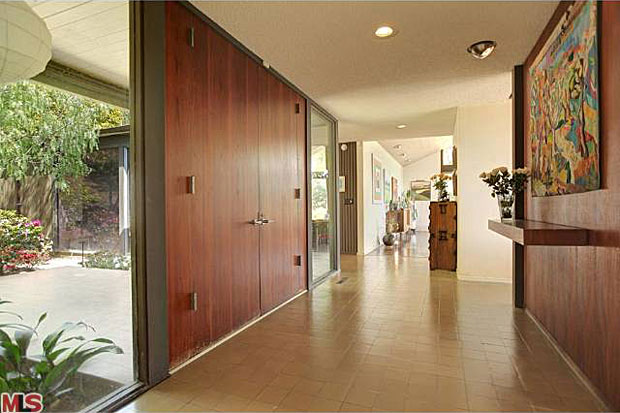 The foyer enjoys an abundance of light thanks to the fantastic glass walls that flank its regal, oversized front door.