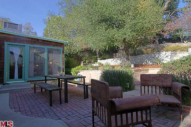 The backyard, which is fairly deep with a gentle slope, includes a dining terrace with fountain and reservoir views.
