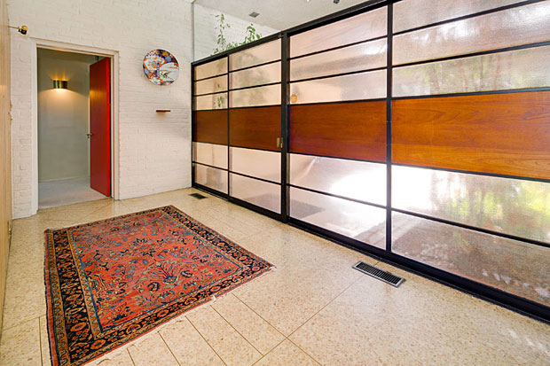 The entry is marked by an elegant – no, make that totally badass – steel-framed wall of glass and wood, with a door that slides open instead of swinging. And terrazzo lines the ground beneath your feet before you even enter.