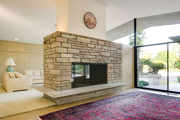 A massive and beautiful fireplace made of stacked granite, and featuring a raised concrete hearth, serves both the living room and den. At one end of the fireplace are hidden built-ins, a design idea that's found throughout the home.
