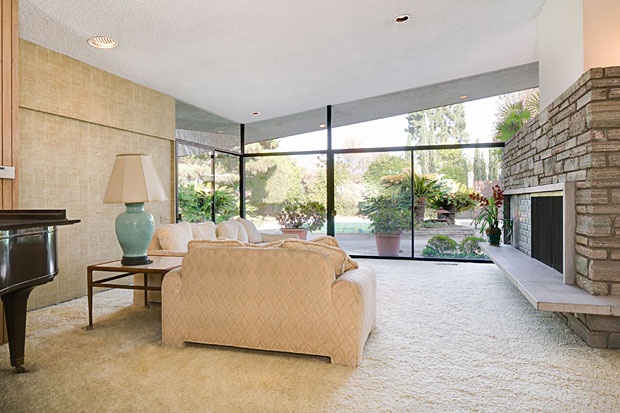 Both the living room and den enjoy access to an expansive wrap around patio overlooking the pool and lush gardens.