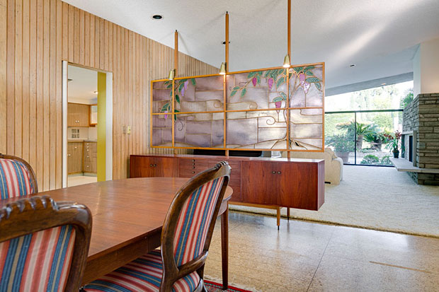 Among the home's many features are teak built-ins, recessed lighting, original Crane fixtures, skylights and this dramatic stained glass separation panel between the dining room and living room.