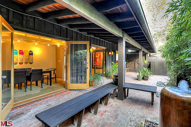 Once inside the gate, you're welcomed into a serene courtyard featuring a brick patio shaded by oversized eaves.