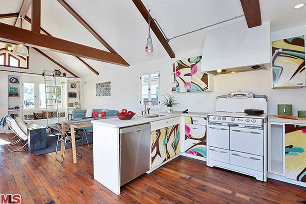 The urban vibe of the cabinets works beautifully against the character of this flawless vintage oven and the white concrete countertops that wrap around the kitchen.