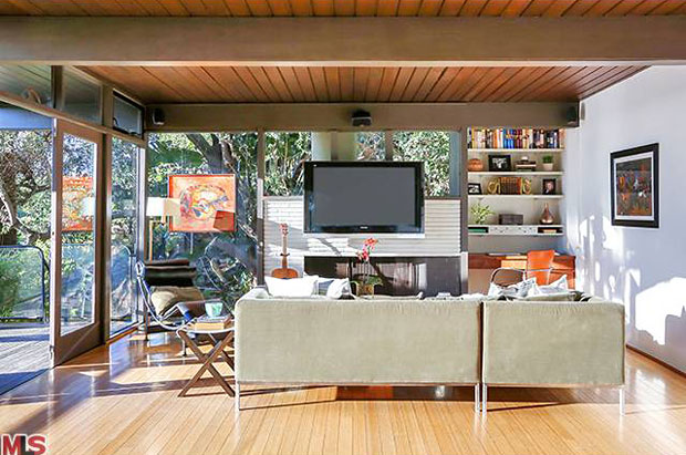 This is a classic Post and Beam design, with angled exterior supports that lend it a confident style worthy of a magazine cover. Built in 1953 by Riley and Levanas, it offers a very open main living area with walls of glass and a balcony that runs the length of the house, which is graced by a canopy of foliage from trees that fill the yard.