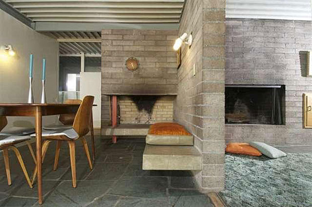 The home has a fireplace in both the living room and dining room, with the two rooms separated by a brick wall extension that features built-in seating made from concrete. Simple and beautiful.
