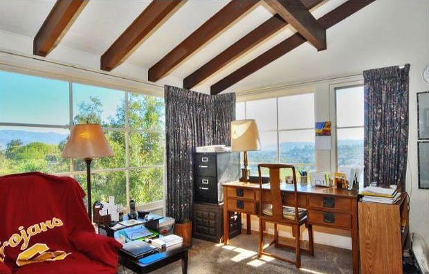 Several of the rooms have views framed by large, corner windows. The expansive views of this room are nicely complemented by its open ceiling with exposed beams.