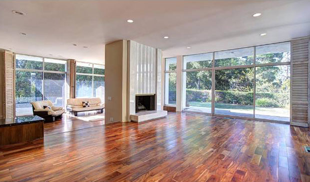 Beautiful hardwood floors and walls of glass are found throughout the home. The travertine fireplace, above, with its fluted overmantel makes a gorgeous centerpiece to this room.