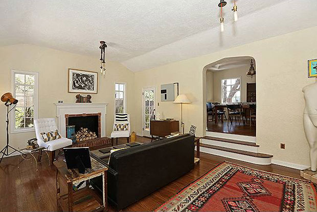 The step-down living room features a coved ceiling, hardwood floors, and dual French doors that open to a sunken patio, perfect for entertaining.