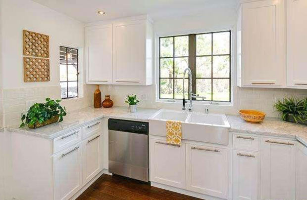 The sparkling kitchen features custom, white shaker cabinets, marble countertops, and the ever-tasteful white subway tiles are used for the backsplash throughout.