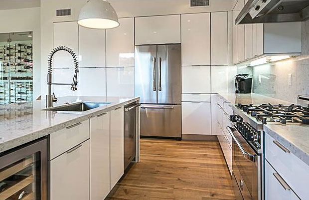The home has been completely remodeled with the finest quality and finishes throughout. The kitchen features top-of-the-line finishes including Carrara marble countertops, Viking appliances, Bertazzoni range, and Uline beverage center under the island.