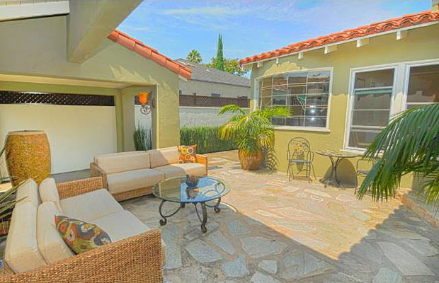The courtyard features a beautiful flagstone patio and is partially covered by Spanish tiled overhangs.