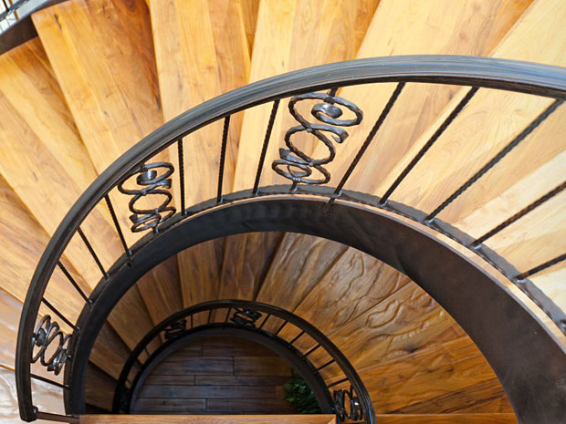 The gorgeous stairway features steps made from hewn walnut and a custom wrought iron railing.