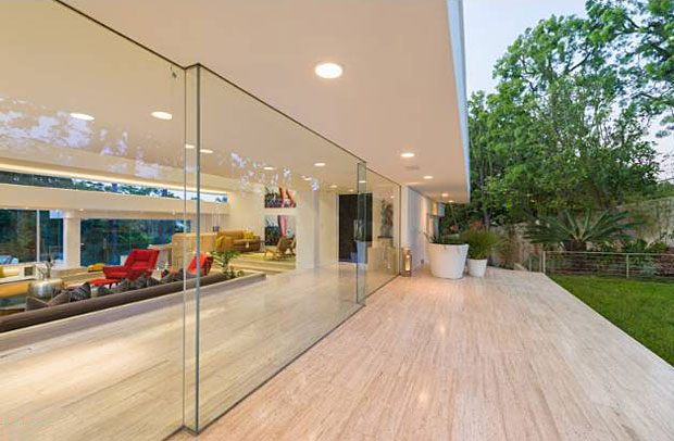 The property occupies nearly an acre of land and the home enjoys total privacy thanks to the beautiful, mature trees that surround it. Capitalizing on that, these floor-to-ceiling walls of glass completely dissolve the boundaries between indoors and outdoors to maximize one's experience of the property.