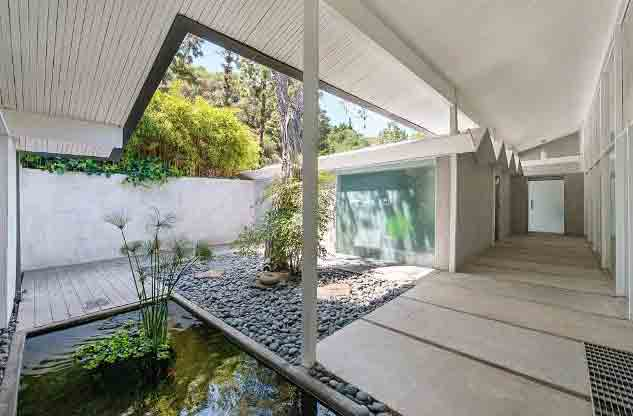 The long walkway from the garage to the front door is covered and ends at a courtyard with a lovely stone-bordered koi pond at the home's entry.