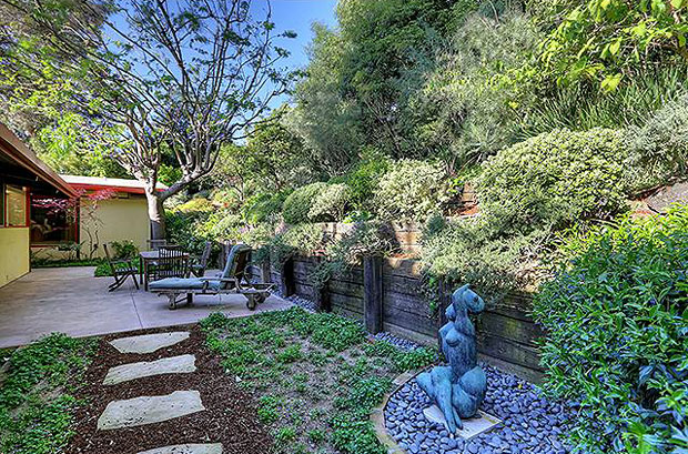 One the outside, the home features a patio, detached promontory deck with an in-ground spa, and a terraced garden.