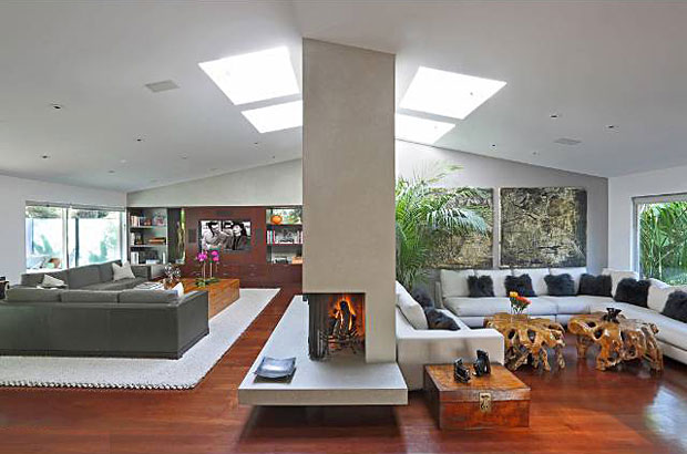 """Originally built in 1957, the home was re-imagined from the studs up with a """"Contemporary Balinese"""" flair. Once inside, you are immediately greeted by a spacious, open floor plan that includes a living room and family room divided by a concrete wall accommodating a sleek fireplace at its corner, as well as built-in shelves and a large cut-away section that connects the two spaces."""