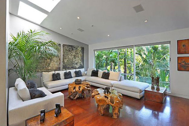Both rooms have walls of glass – one surrounded by the greenery of tropical forest, the other opening to a backyard oasis. If the natural light provided by the walls of glass isn't enough, the vaulted ceiling connecting the two rooms features skylights on both sides.