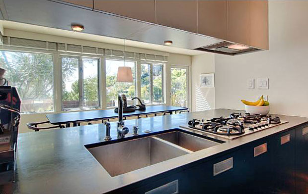 The modern, utilitarian kitchen is enhanced with views of downtown and expansive terraced gardens.