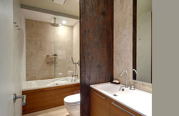 The updated bathrooms boast a chic, modern style with finishes that include a teak sink, reclaimed wood wall and boffi fixtures.