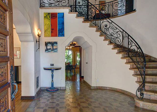In a word, this two-story foyer is resplendent. From the tiles on the floor, all the way up to the coffered ceiling with its hand-painted beams and panels, there is beauty everywhere you look. Check out the swirls of the wrought iron railing adorning the curved staircase and the spiral posts lining the hallway upstairs.