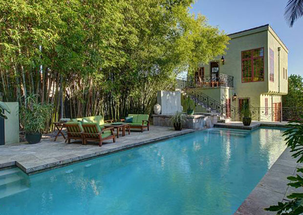 The pool, surrounded by lush landscaping and a travertine deck, is a genuine oasis.