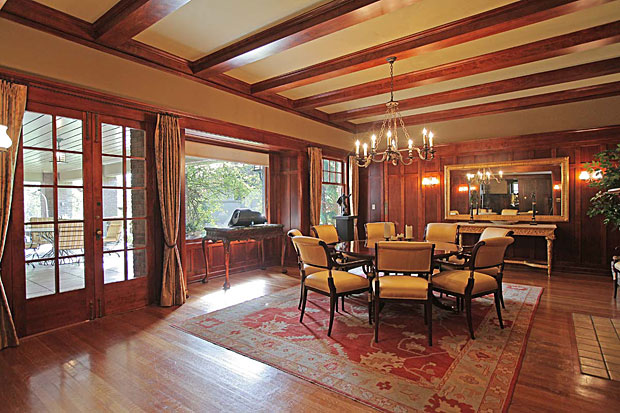 The home features extensive use of beautiful woods, including mahogany and Oregon pine. The banquet-sized dining room, pictured here, includes a fireplace and French doors that open up to the veranda.