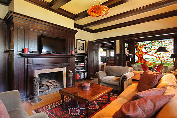 """The home's library, with wood paneled walls and fireplace, also features a massive stained glass window to create """"fiery gems for you"""" (as Graham Nash once sung)."""