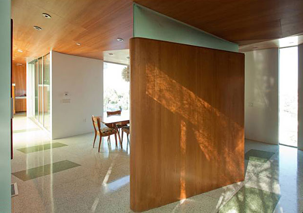 Using the same wood, the ceilings of the living room, dining room and kitchen are covered in faceted, origami-like panels that undulate overhead and provide a warm contrast to the terrazzo floors.